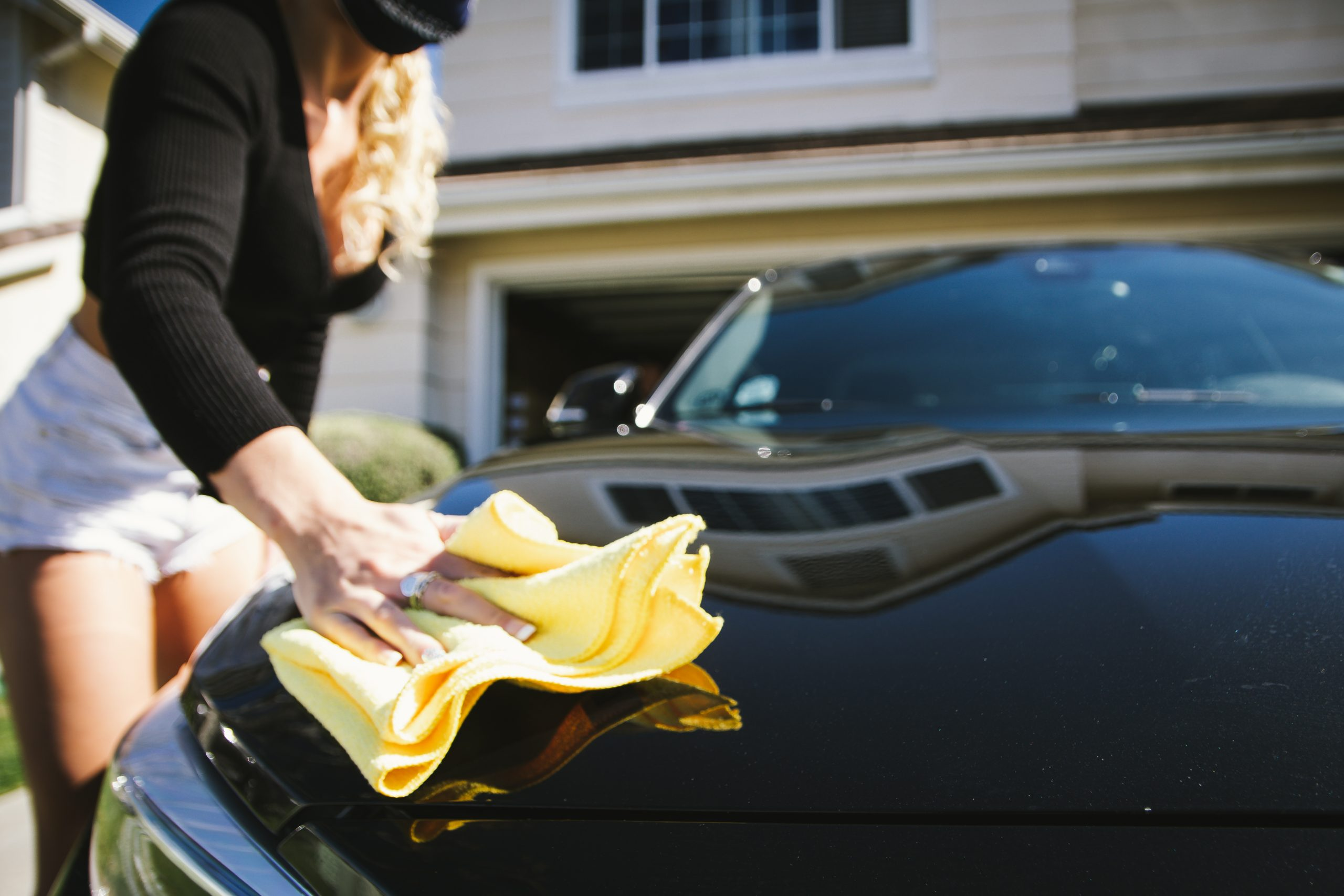 wiping down bmw m2 with quick detailer and microfiber towel